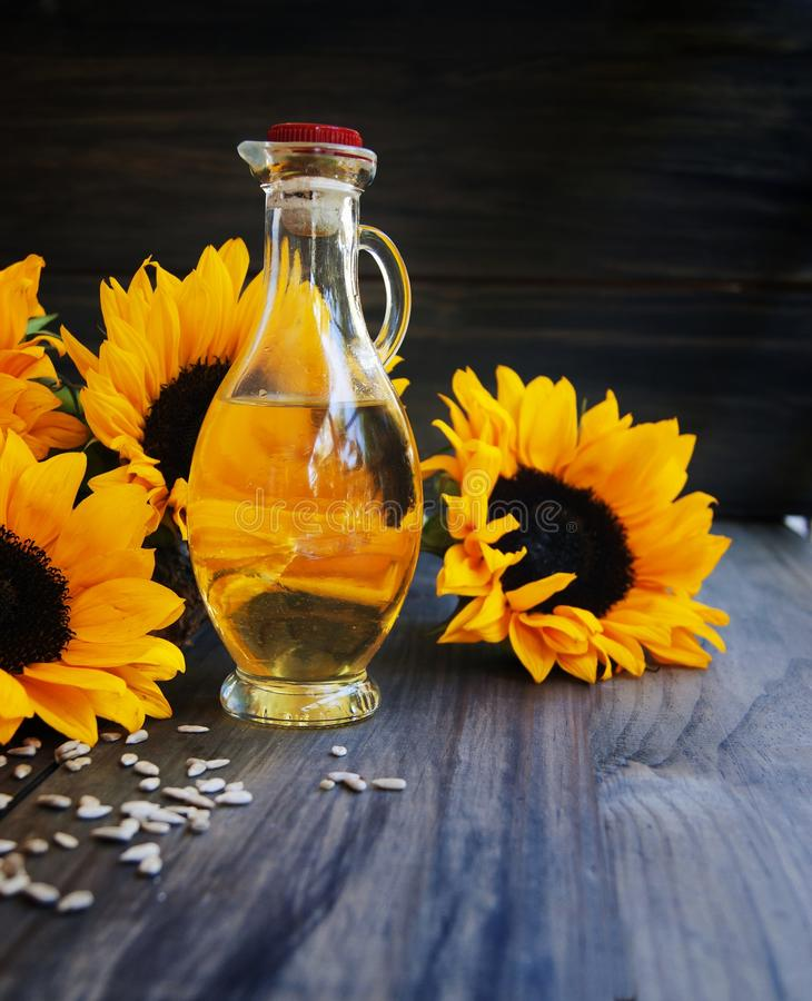 Sunflowers, sunflower seeds and a bottle of. Oil on a wooden background stock images