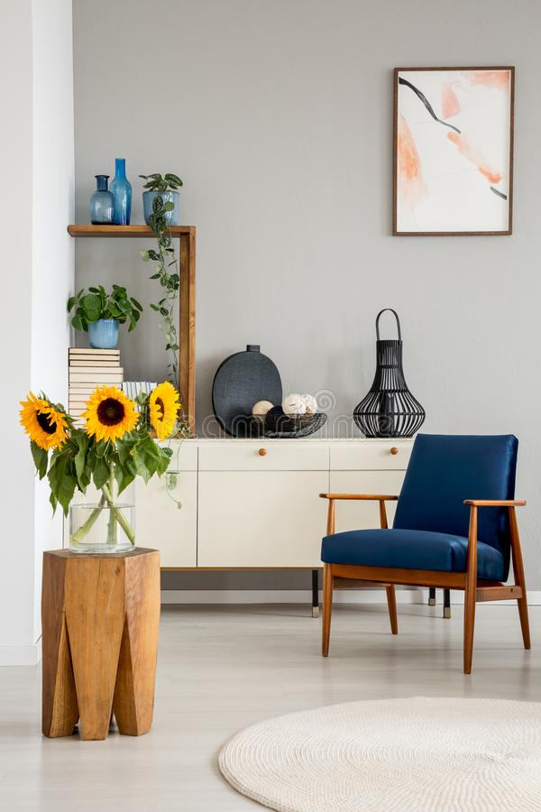 Sunflowers on wooden stool near blue armchair in grey living room interior with poster. Real photo royalty free stock image