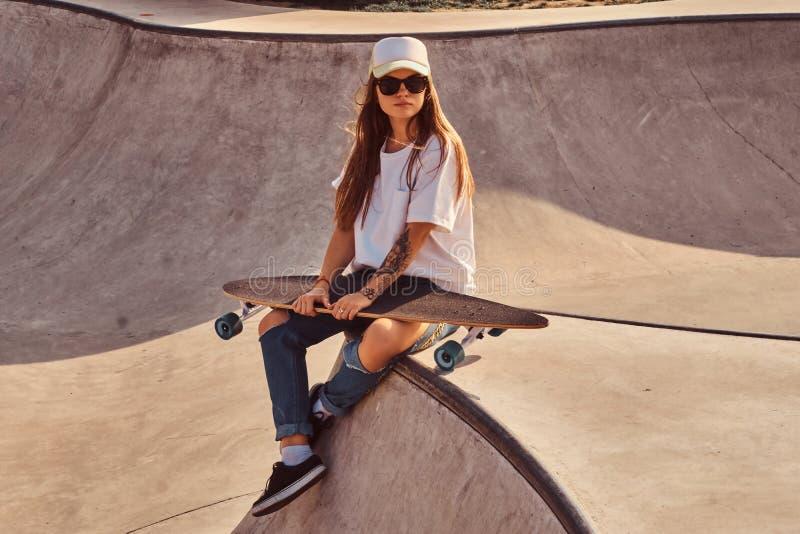 sunglacces和盖帽的美丽的年轻女人坐在skatepark 库存图片