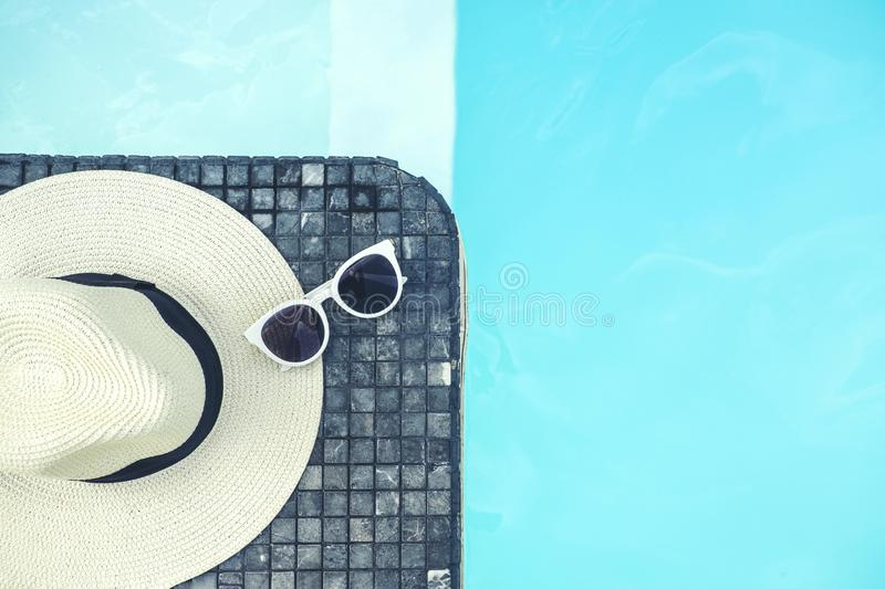 Sunglass and Hat on luxury swimming pool tropical beach resort , summer concept royalty free stock images