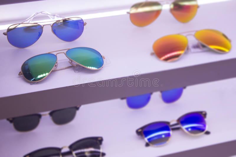 Sunglass shop with sale on high quality lenses on rack. Blue an stock images