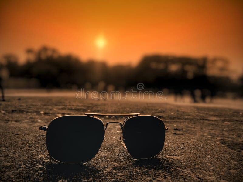 sunglass und Sonnenuntergang stockbild