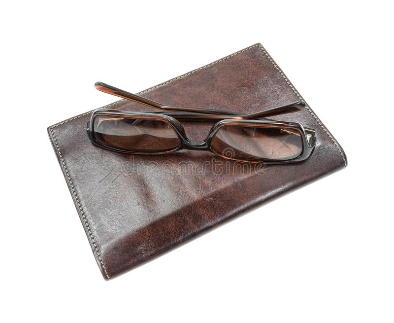 Sunglasses atop billfold. A used pair of sunglasses atop a brown leather billfold on a white background stock images
