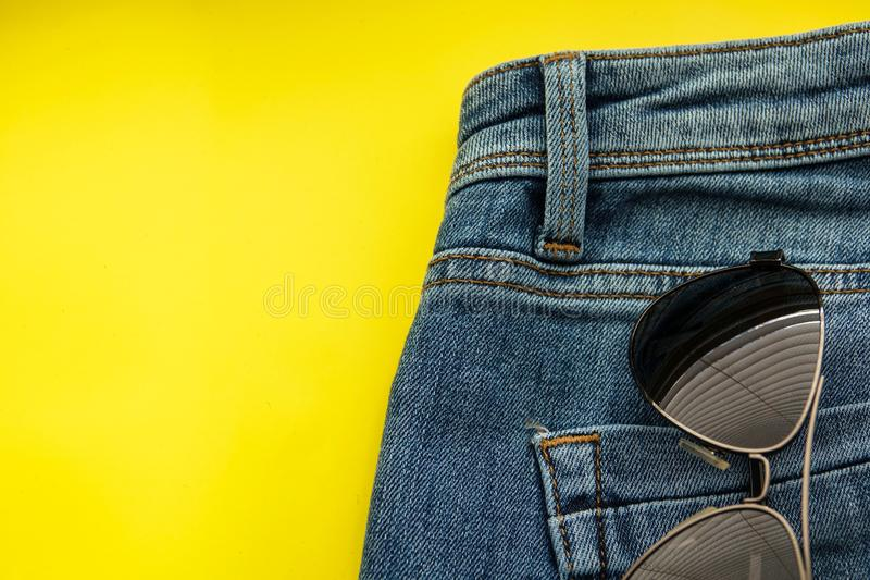Sunglasses in back pocket of shorts blue jeans. Sunglasses in back pocket of blue jeans closeup cloth clothing cotton denim detail fashion pants style wear royalty free stock images