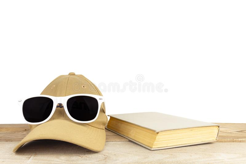 Sunglasses, baseball cap, book, lie on wooden boards on a white background royalty free stock photography