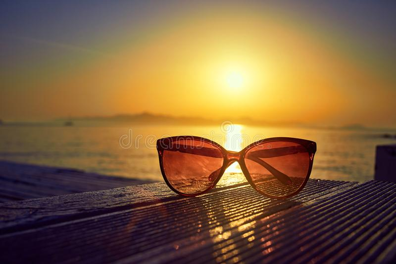Sunglasses on beach at sunset. Summer background concept. Sunglasses on beach at sunset . Summer background concept stock image