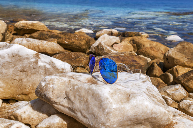Sunglasses blue aviator on the beach rocks stock photo