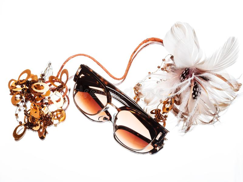 Sunglasses with brown glasses and a flower on a white background stock image