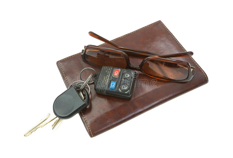 Sunglasses and car keys atop billfold. A pair of used sunglasses and car keys atop a leather billfold on a white background royalty free stock photography