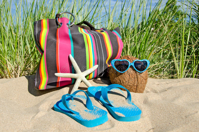 Sunglasses on a coconut. Coconut wearing sunglasses on a beach with starfish, beach bag and flip-flops royalty free stock photography