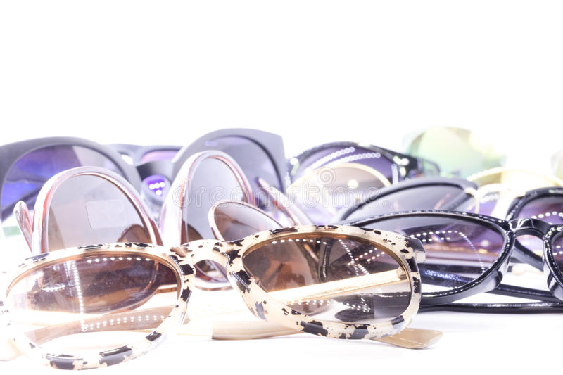 Sunglasses. Collection of assorted styles of tinted sunglasses on white background stock images
