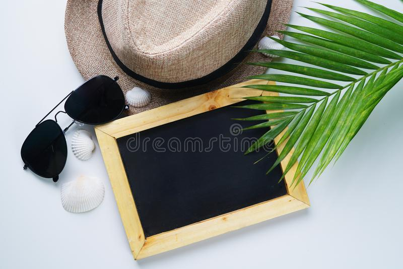 Sunglasses, Fedora Hat, Palm Leaf, Sea Shells and Blackboard Room for Text. Flat Lay Traveling Holiday Vacation Background stock photos
