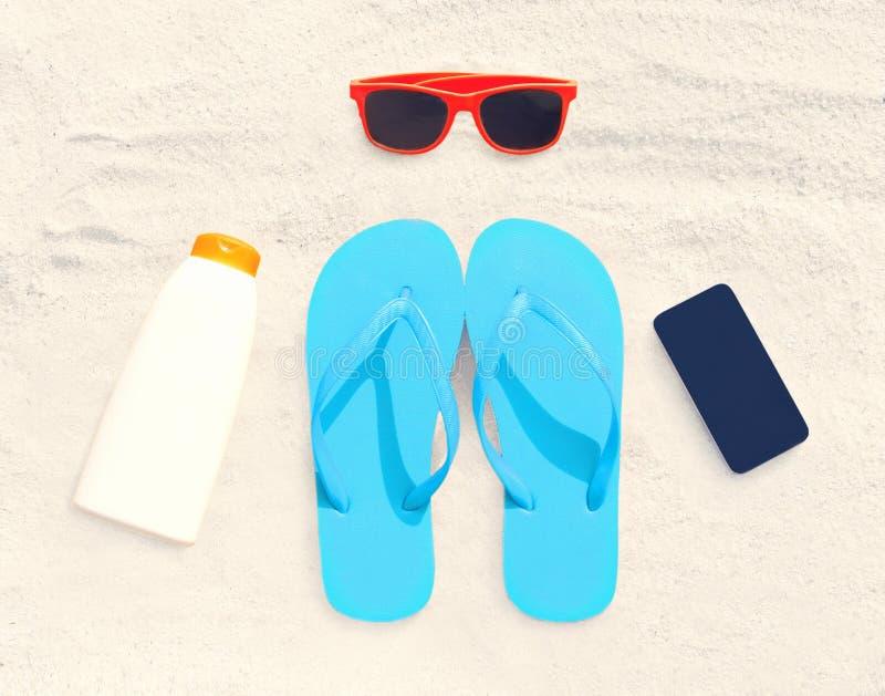 Sunglasses, frameless smartphone, sunscreen bottle, red flip flops. On white sand beach background royalty free stock images