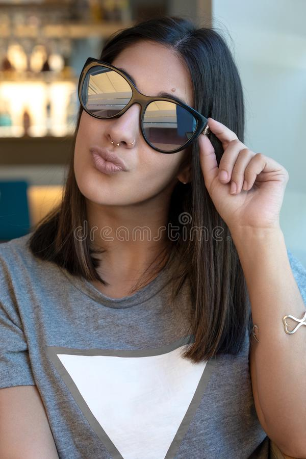 Sunglasses girl kissing at camera royalty free stock photography