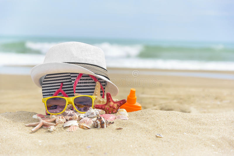 Sunglasses and a hat on the beach. Sunglasses and a hat on a background of sea shells on royalty free stock image