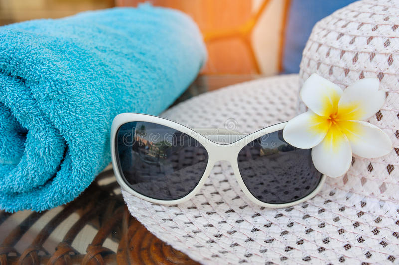 Sunglasses are on the hat and flower on beach royalty free stock images