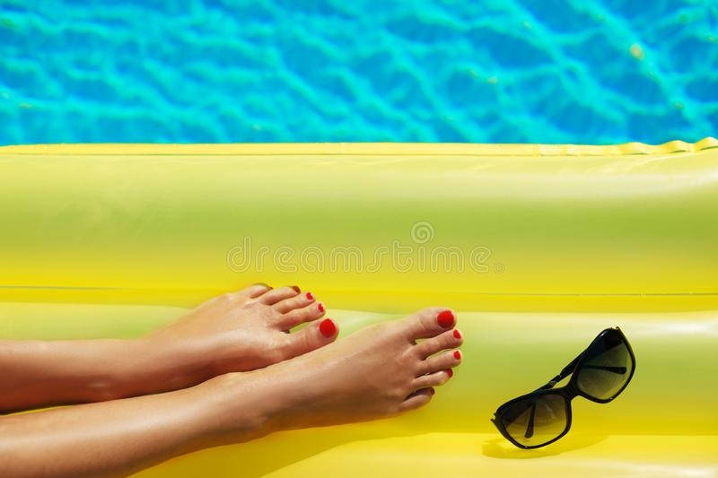 Sunglasses and inflatable matress. Legs close up. Creative gel royalty free stock image