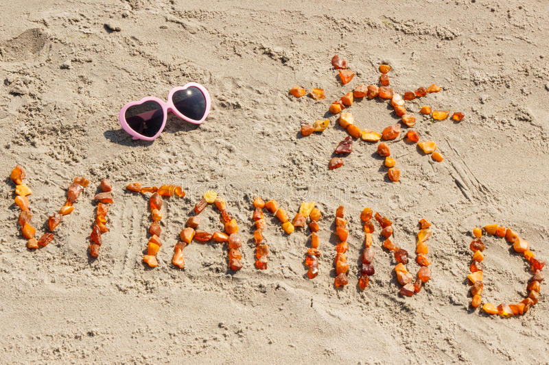 Sunglasses, inscription vitamin D and shape of sun at beach, concept of summer time and healthy lifestyle royalty free stock photos