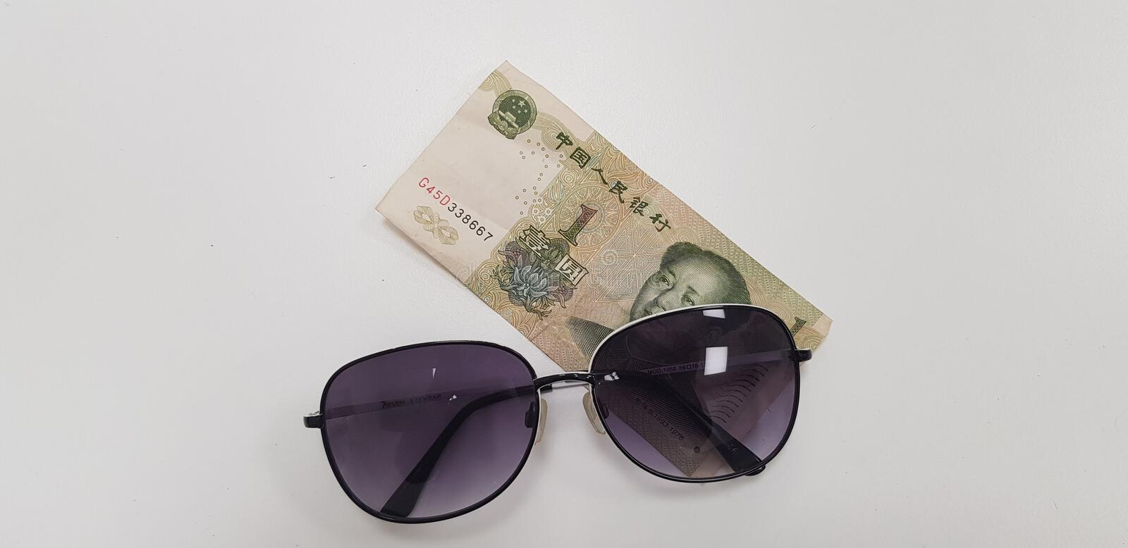 One yuan banknote on white table. Sunglasses lay on one yinhang banknote on white table bookmaker brokerage budget business capital china currency day earn stock images
