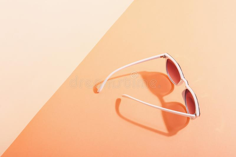 Sunglasses lie on a colored background casting a harsh shadow, concept art of summer and relaxation, minimalism. Sunglasses lie on colored background casting a royalty free stock images