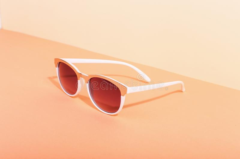 Sunglasses lie on a colored background casting a harsh shadow, concept art of summer and relaxation, minimalism. Sunglasses lie on colored background casting a royalty free stock photography