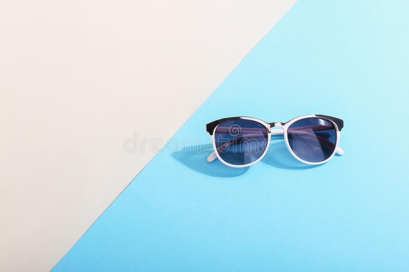 Sunglasses lie on a colored background casting a harsh shadow, concept art of summer and relaxation, minimalism. Sunglasses lie on colored background casting a stock photos