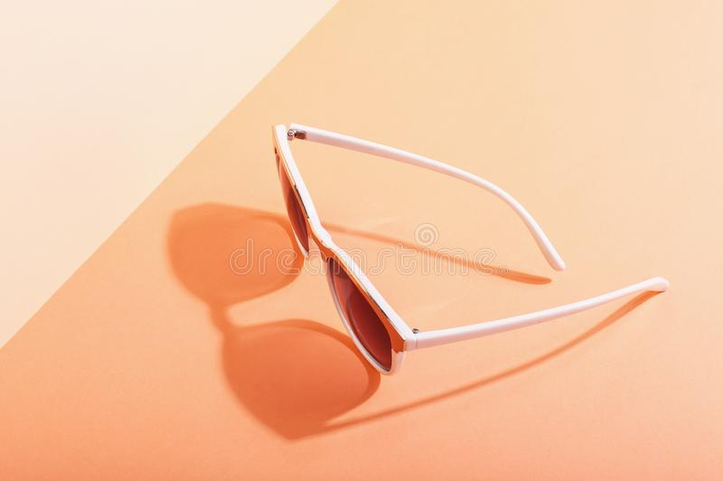 Sunglasses lie on a colored background casting a harsh shadow, concept art of summer and relaxation, minimalism. Sunglasses lie on colored background casting a royalty free stock photo