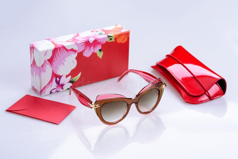 Sunglasses in a modern frame, box, pouch and envelope on a white glossy background with reflection royalty free stock photo