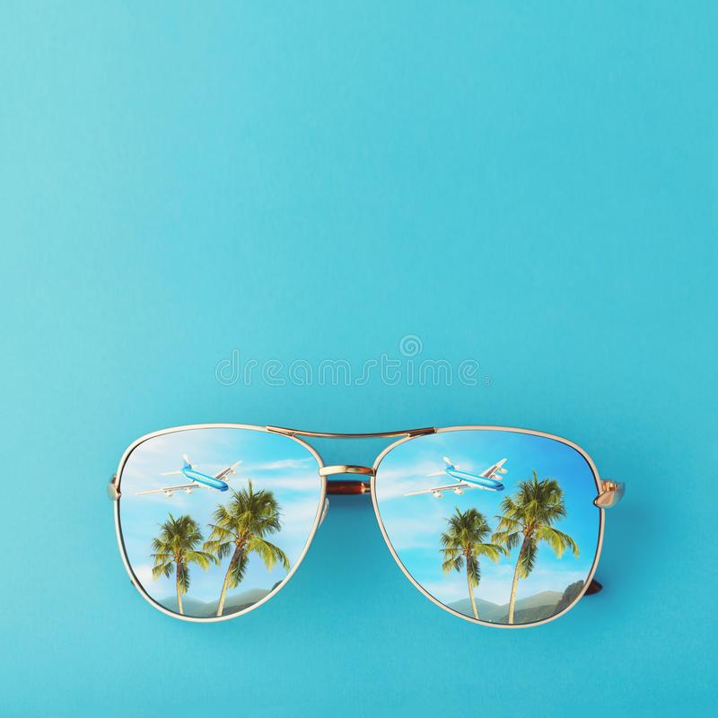 Sunglasses with palm trees, a plane and mountains reflected in them. Concept on the theme of vacation and travel with copy space. Top view royalty free stock image