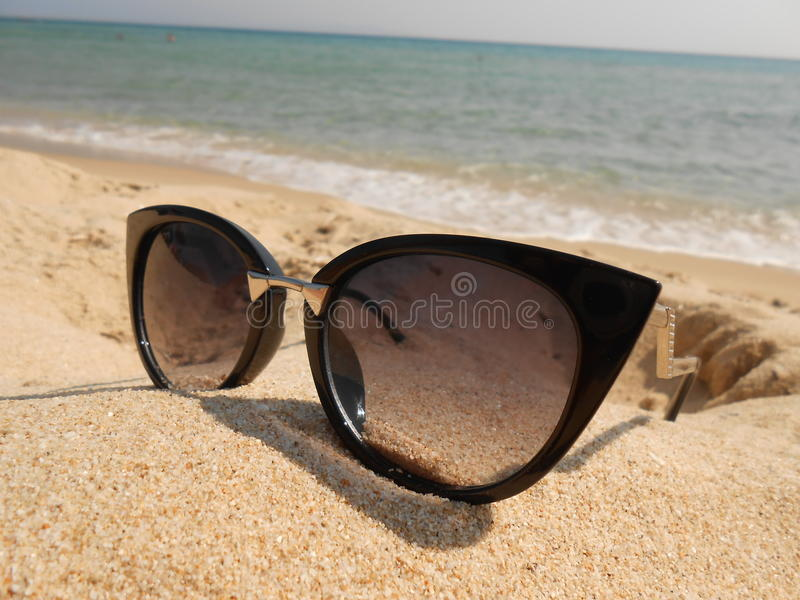 Sunglasses. Photography of black luxury sunglasses on sand, fashion detail for modern women, close up royalty free stock photos