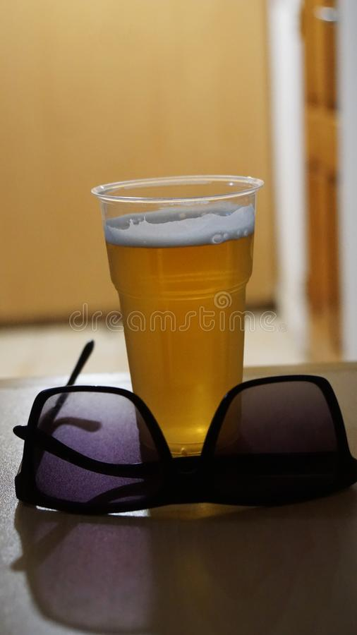 Sunglasses and a plastic beer glass stock photos