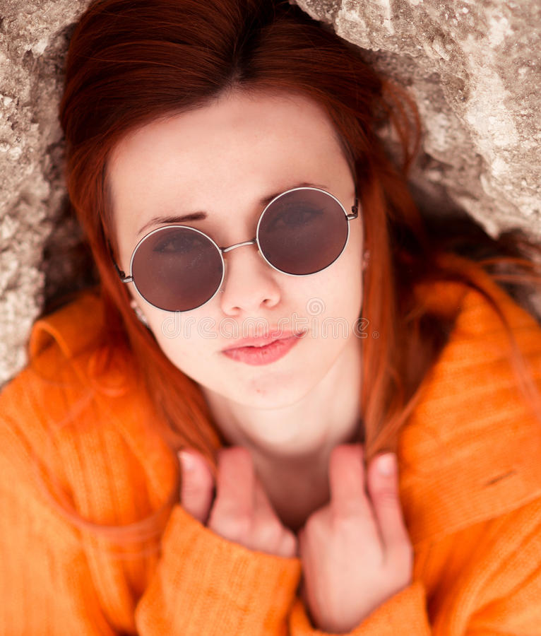 Portrait of beautiful, attractive red-haired, girl with modern round sunglasses royalty free stock image