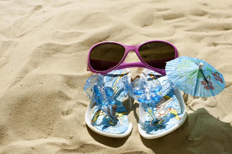 Sunglasses And Sandals On Beach Royalty Free Stock Photography