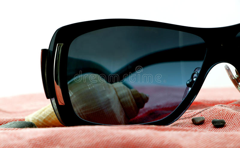 Sunglasses and seashell on a beach towel. A composition with a pair of fashion sunglasses and a seashell on a red beach towel, detail, white background royalty free stock images