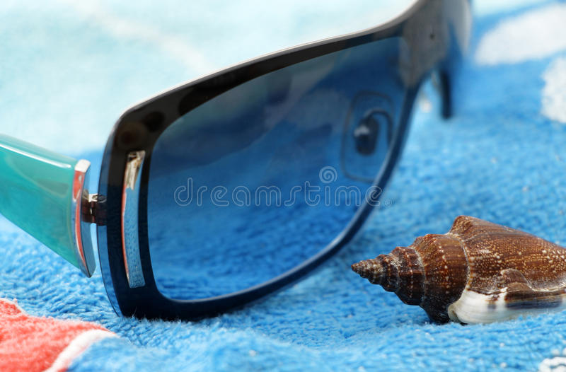 Sunglasses and seashell on a beach towel. Foreshortened view of a composition with a pair of sunglasses and a seashell on a blue and red beach towel, detail stock photos