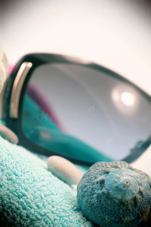 Sunglasses and seashell, vintage style. A composition with a pair of fashion sunglasses and a seashell on a blue beach towel, detail, white background, portrait royalty free stock photo