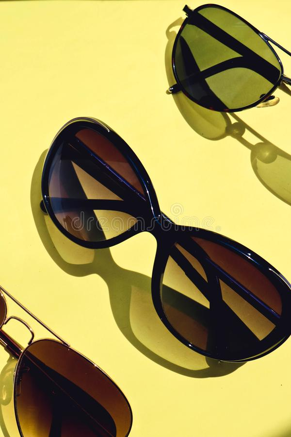 Sunglasses with shadows on colorful yellow background stock images