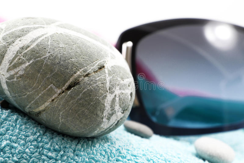 Sunglasses and stones on beach towel. Perspective view of a composition with a pair of fashion sunglasses and some stones on a blue beach towel, detail royalty free stock photos
