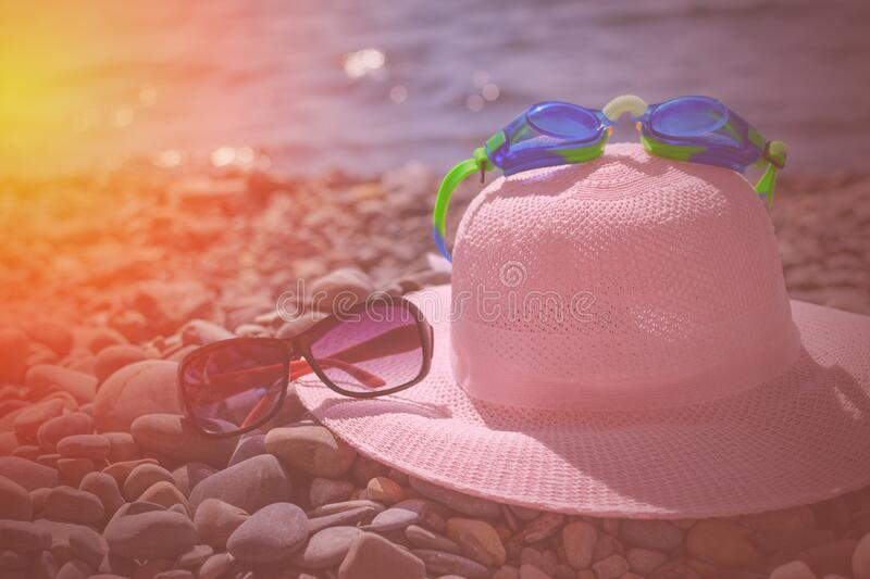 Sunglasses, a straw hat, swimming glasses lie on a pebble beach by the sea during the day. Rest by the sea on the warm stones. Swimming and sunglasses on the royalty free stock images