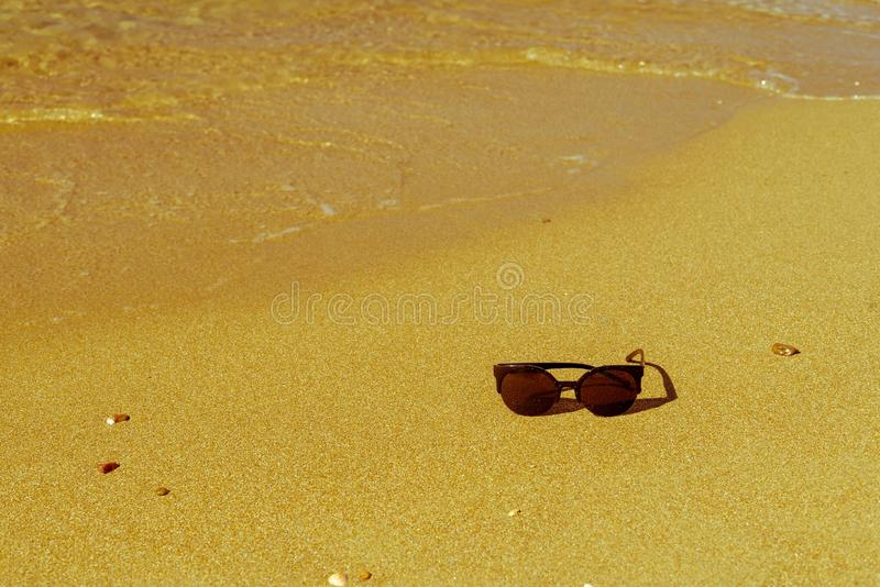 Sunglasses and water on sandy beach. Natural background and one black sunglasses with water of a sea wave on the sandy beach of the resort royalty free stock photography