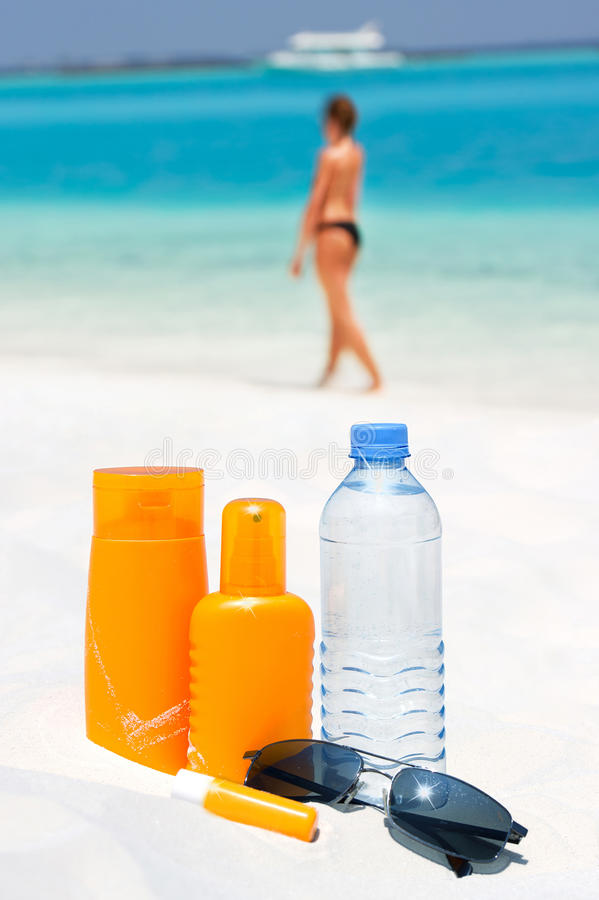 Sunglasses, water and sun protection cream. On beach background stock images