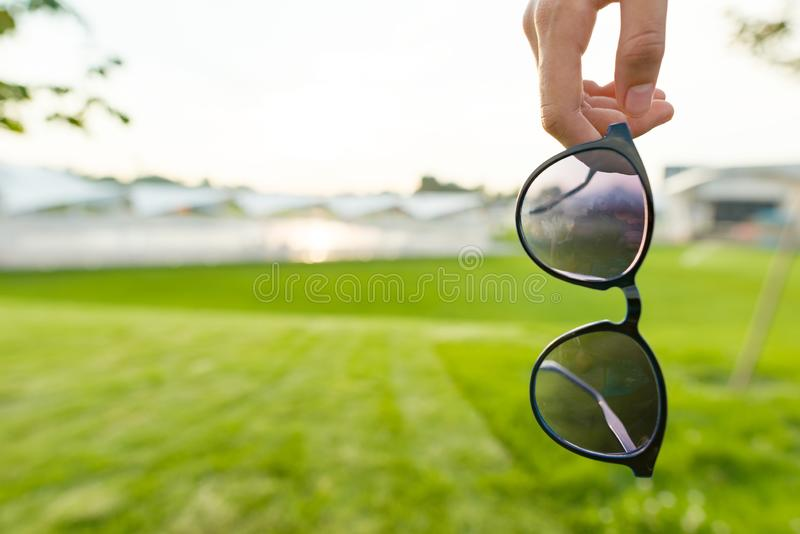 Sunglasses in woman hand close up, copy space, summer green grass background. Sunset sky royalty free stock images