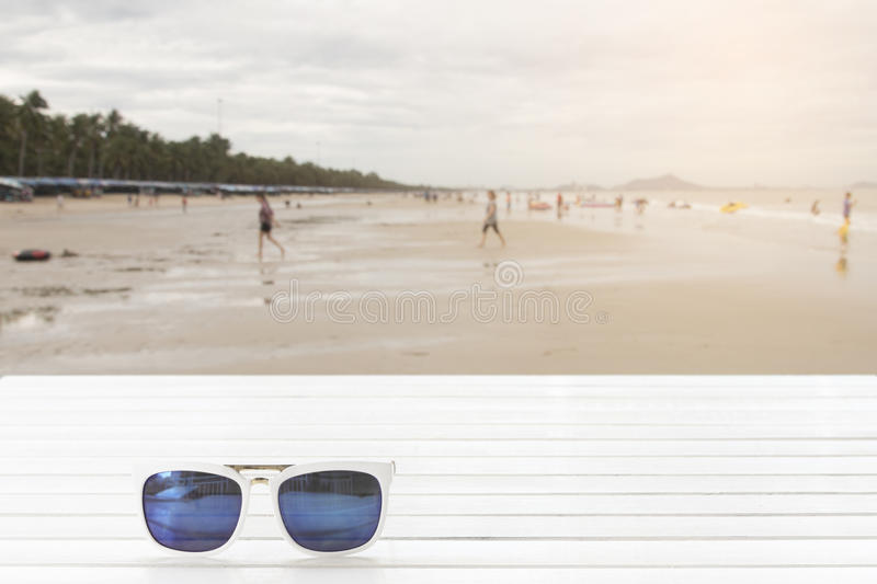 Download Sunglasses On Wooden Table With Of People On The Beach Stock Photo - Image of seaside, accessory: 83708252