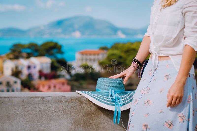 Sunhat azul que pone en la pared de la acera Mujer turística que disfruta de vista del pueblo tranquilo colorido Assos el día sol fotos de archivo