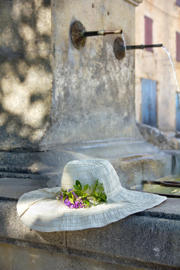 Sunhat with real flower on a Provencal fountain in Porvence, France. royalty free stock image