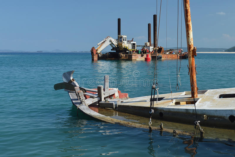 Sunk wooden boat and old rusty dredger. Sunk ruined wooden boat and old rusty dredger in calm blue bay, peacefull sunny day royalty free stock image