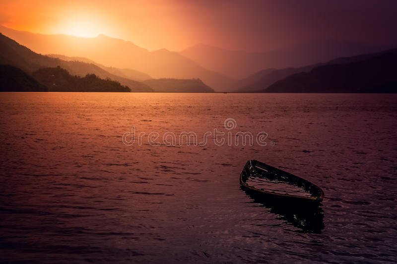Sunken boat. At the lake in Pokhara at sunset, Nepal stock photography