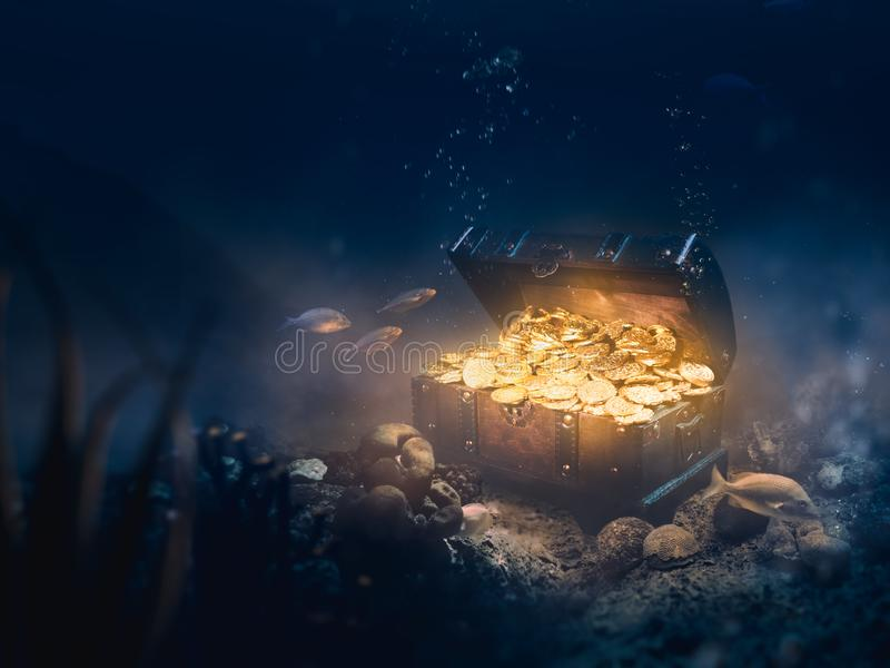 Sunken treasure at the bottom of the sea. Open treasure chest sunken at the bottom of the sea / high contrast image stock photography