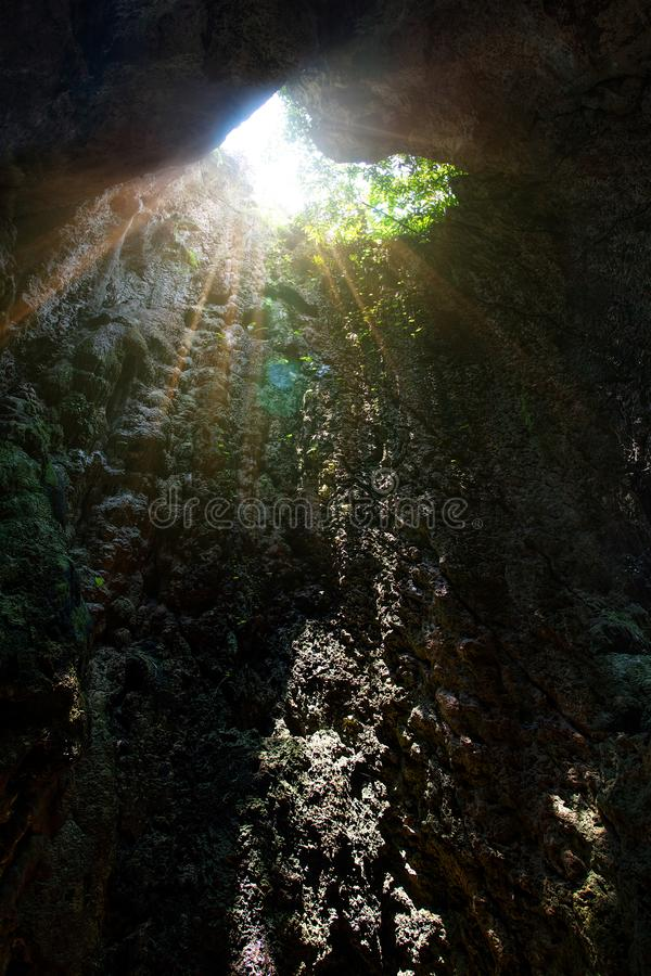 Sunlight burst or sun flare coming from top of underground cave mouth opening. royalty free stock photo