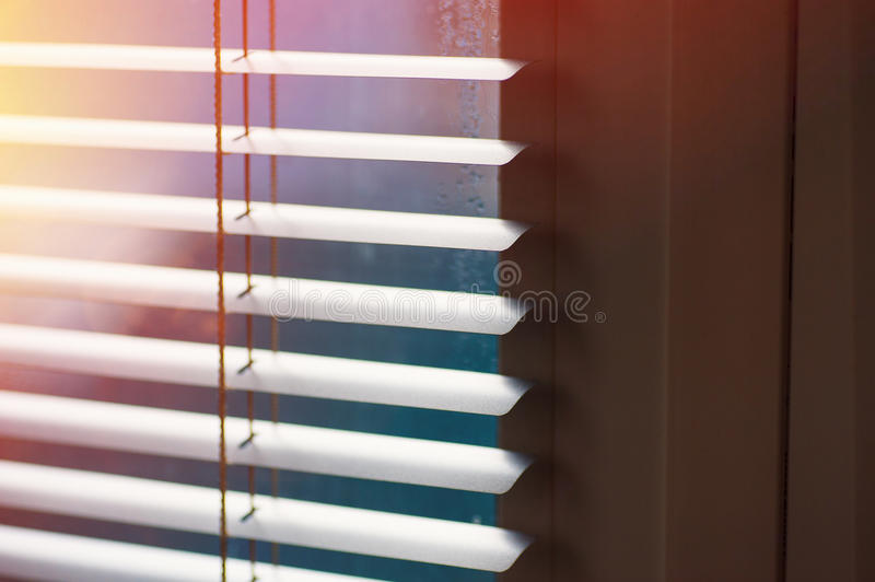 Sunlight coming through venetian blinds by the window stock photography